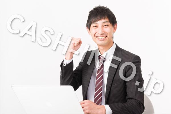 パソコンを見てガッツポーズをするスーツの男性