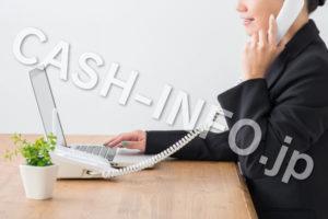 黒スーツでパソコンしながら電話する女性