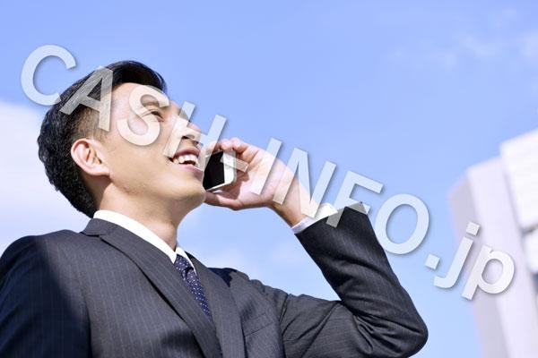 スマホと電話するスーツの男性