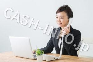 パソコンを見ながら電話をするスーツの女性