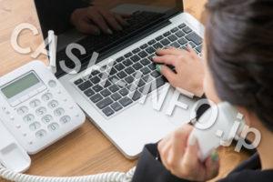 固定電話とパソコンと電話する女性