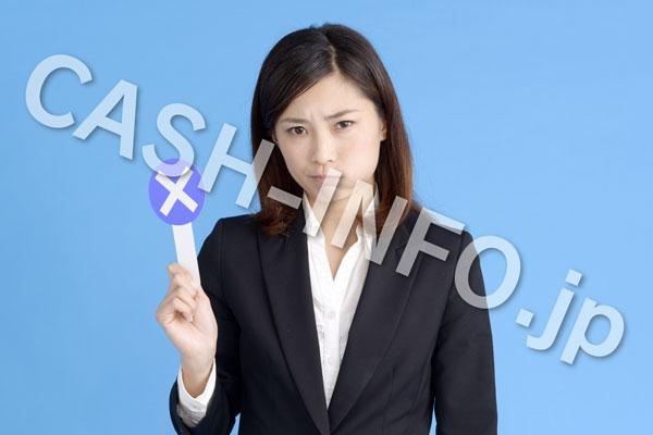 バツを持って怒るスーツの女性