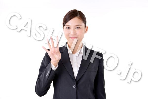 指で4を指すスーツの女性