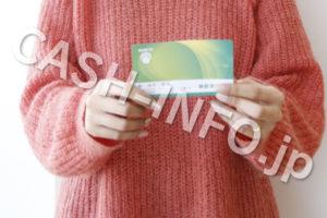 通帳を見るピンクのセーターを着ている女性